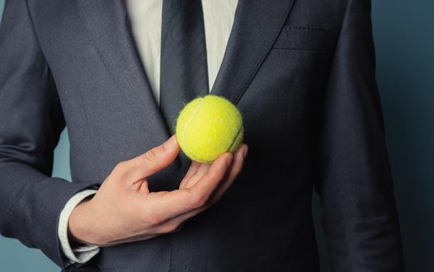 Business man holding a tennis ball