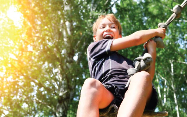 Boy swinging on a rope from a tree