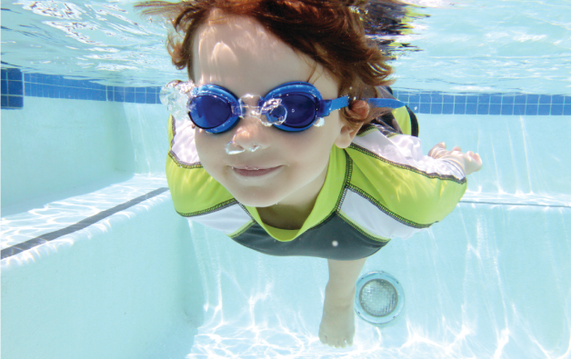 Boy swimming underwater with goggles on