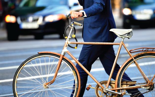 Man in suit walking with bike
