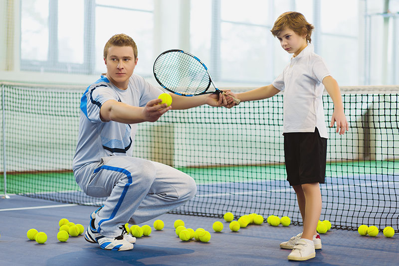 Man and boy playing tennis