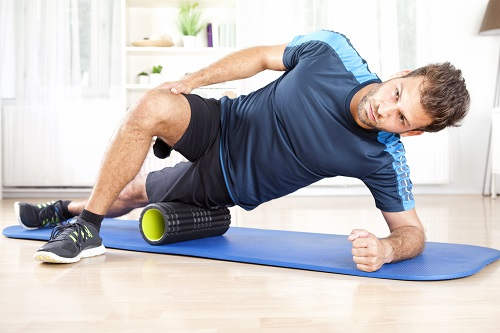 man using foam roller on leg
