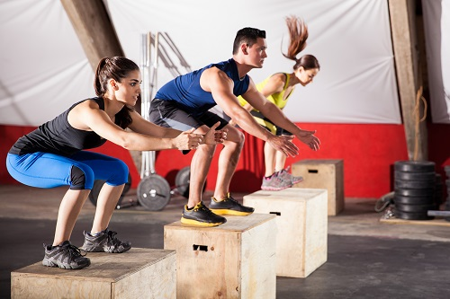 group of people jumping onto box gym