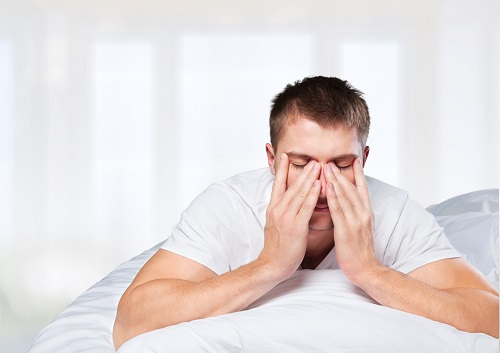 man waking up in white bed