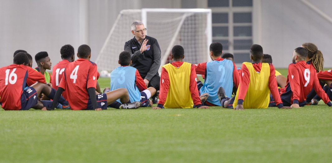 Coach talking to youth football players in front of a goal