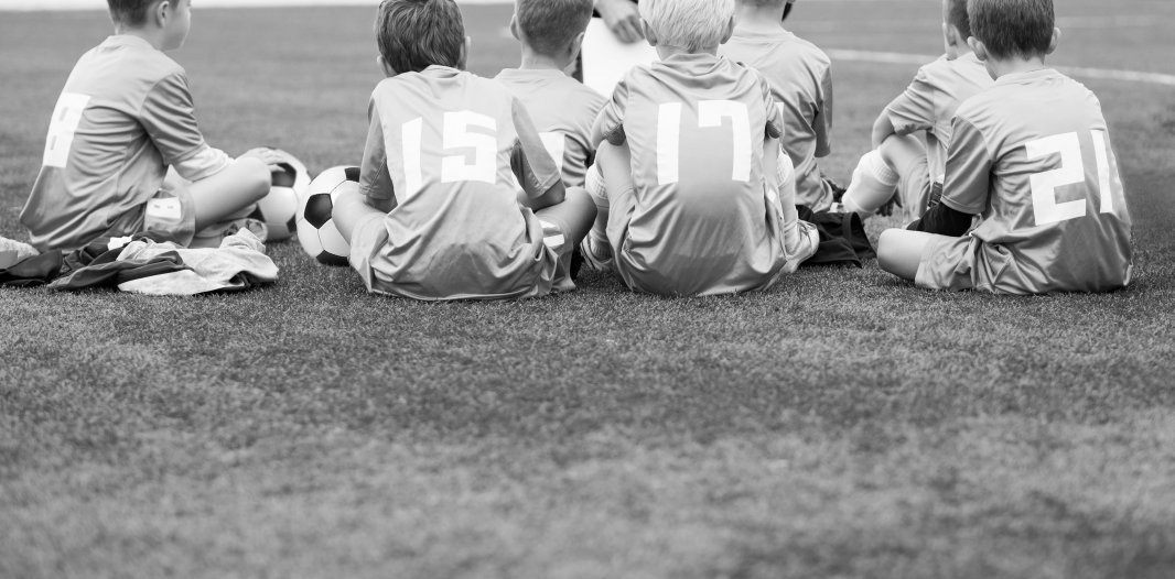 7 Young Boys Sat on the Grass in their Football Kit
