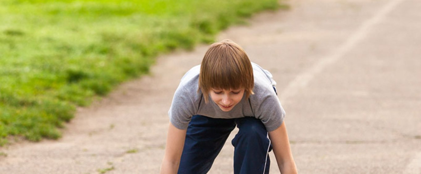 Child about to start running on a track
