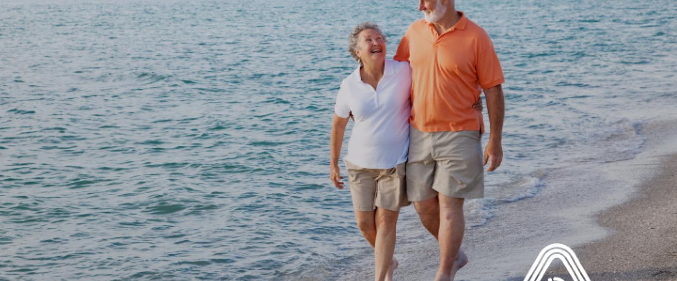 Older couple walking on beach