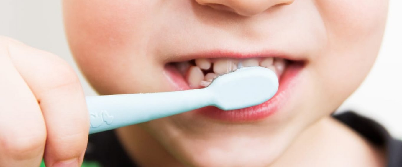 young boy's mouth with toothbrush