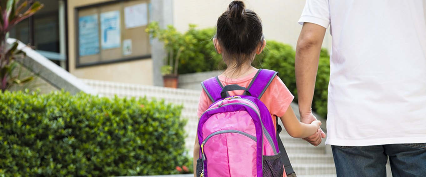 Girl with Pink Backpack Holding an Adult's Hand