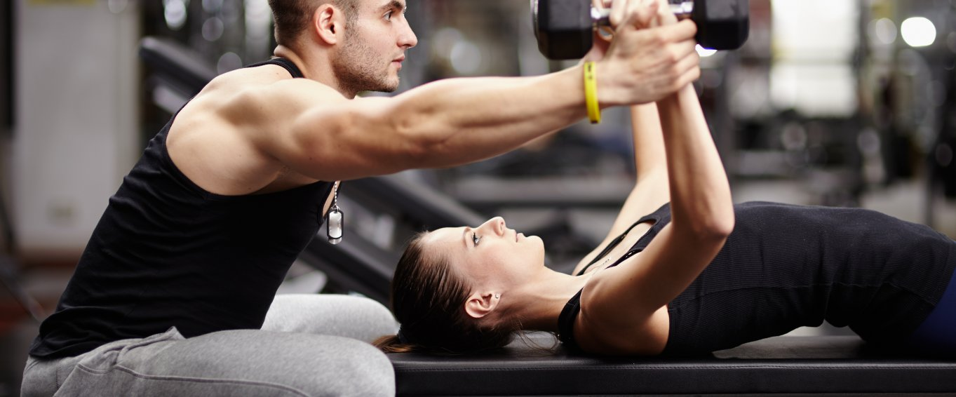 Personal Trainer Helping a Woman Lift Weights