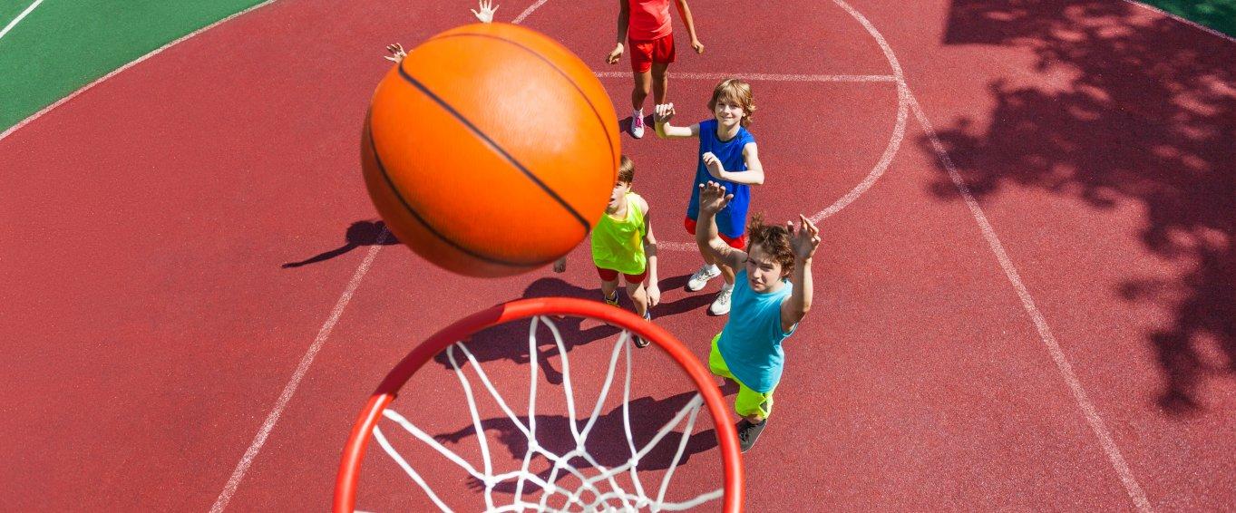 Young Children Shooting Basketball Hoops
