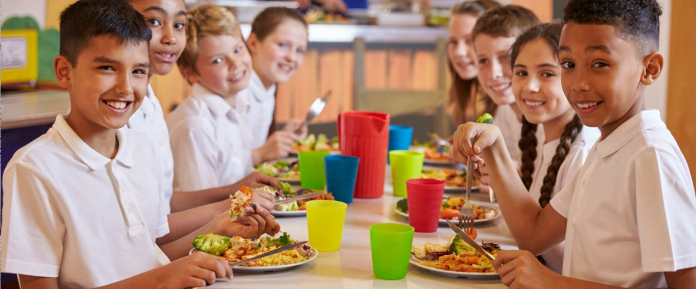 Eight Smiling School Children Eating School Lunch Together