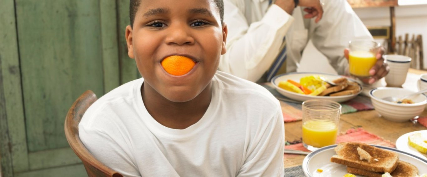 Boy at the breakfast table with an orange in his mouth