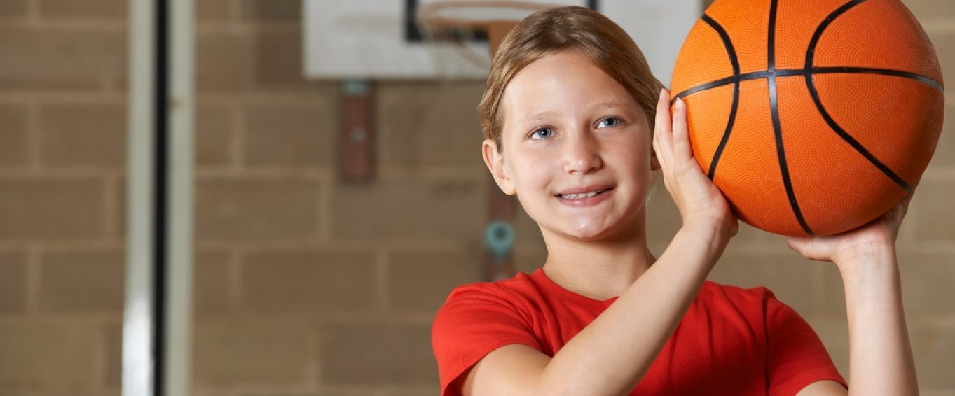 Young Girl Smiling and Holding a Basketball