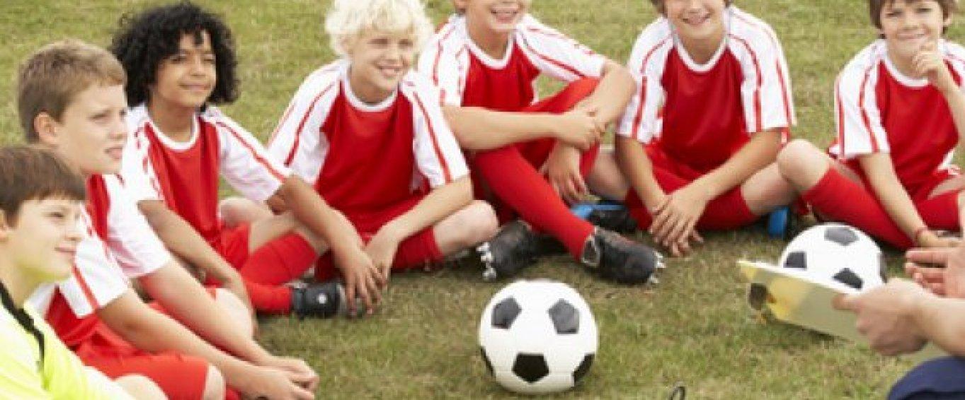 Kids football team sat around a football