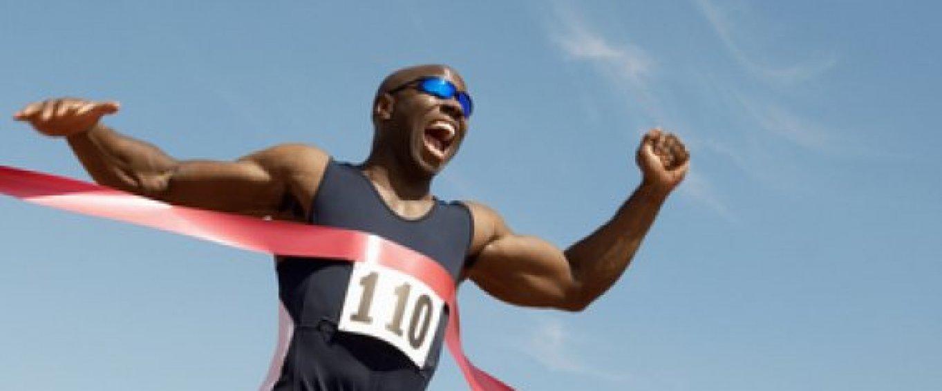 Athlete running through the finish line