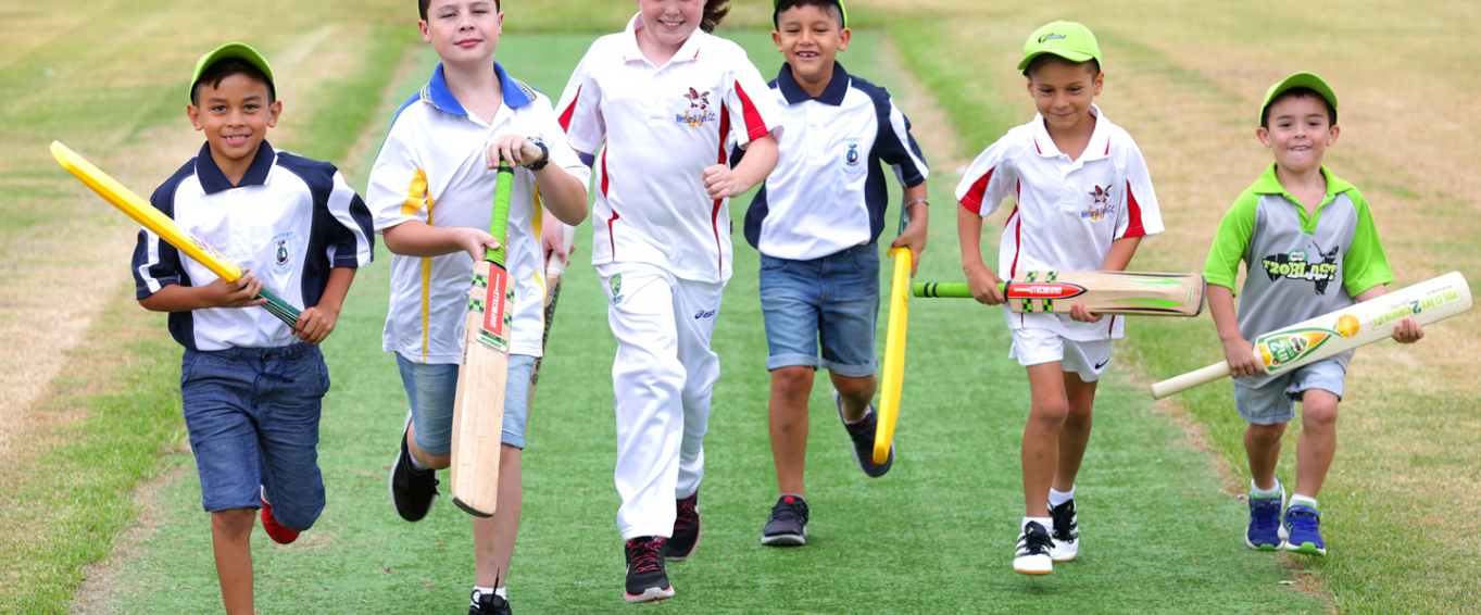 Six young boys running while holding cricket bats