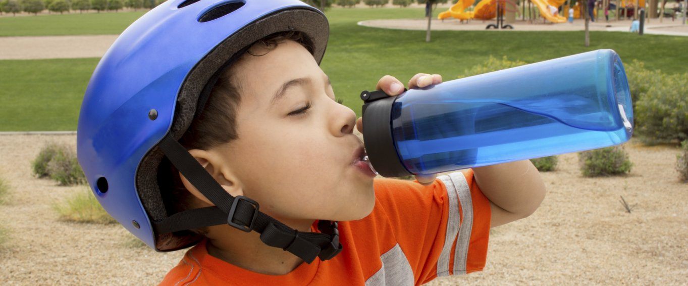 Young Boy in a Blue Bike Helmet Drinking from a Water Bottle