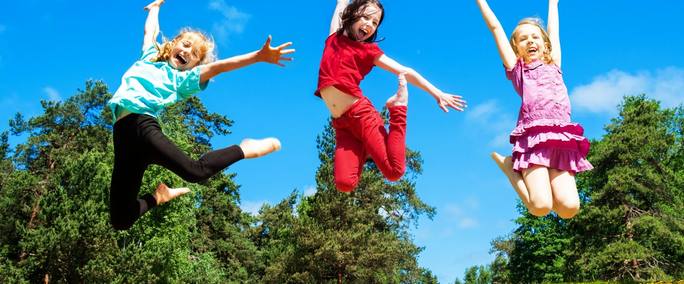 three young girls leaping into the air