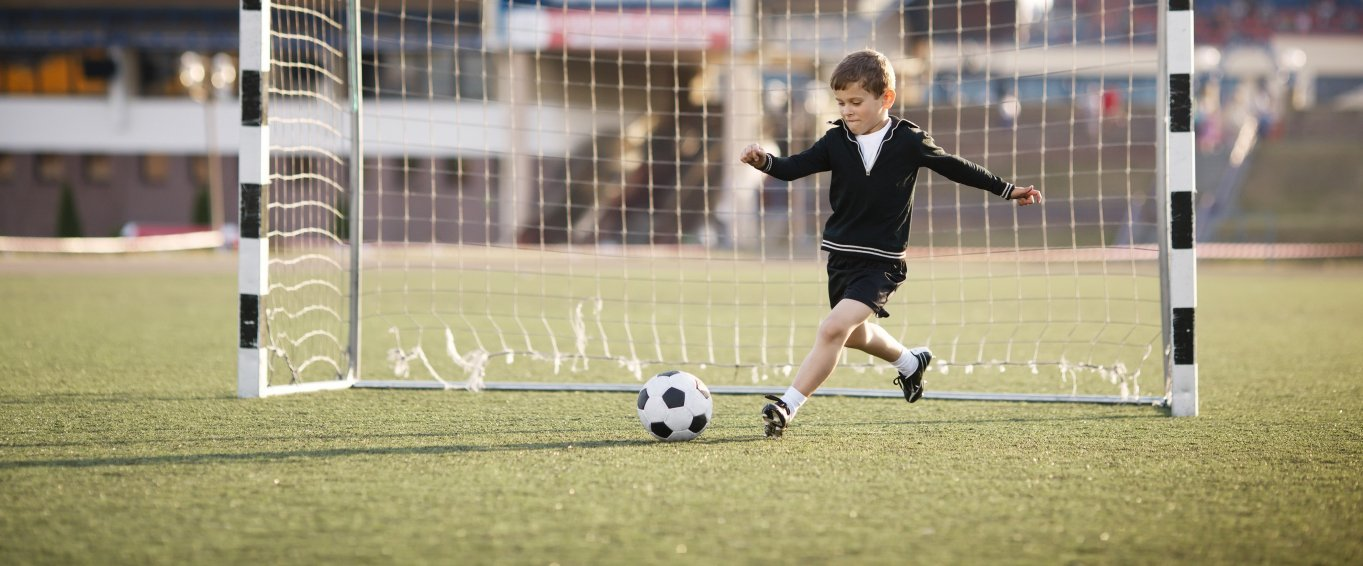 Young Boy Standing in Goal & Kicking a Football