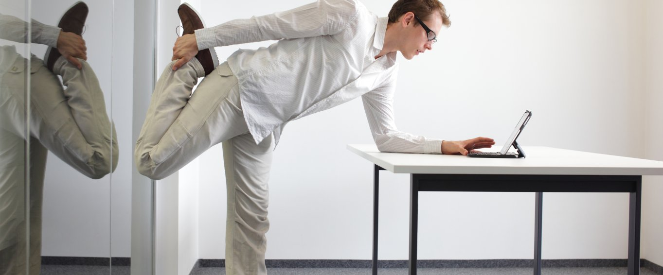 Man in white shirt stretching at desk