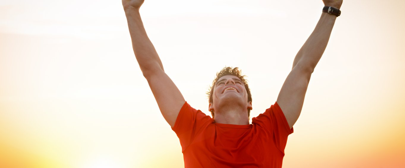 Man in red t shirt celebrating with his arms in the air in front of sunset
