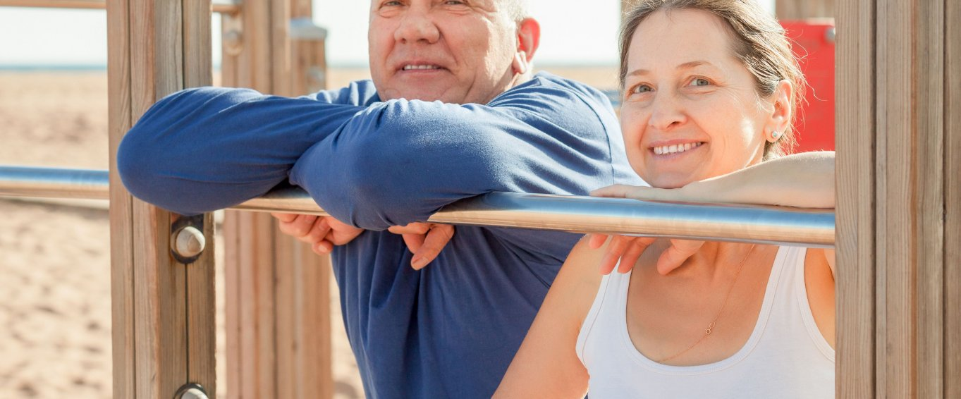 Mature couple training together on beach