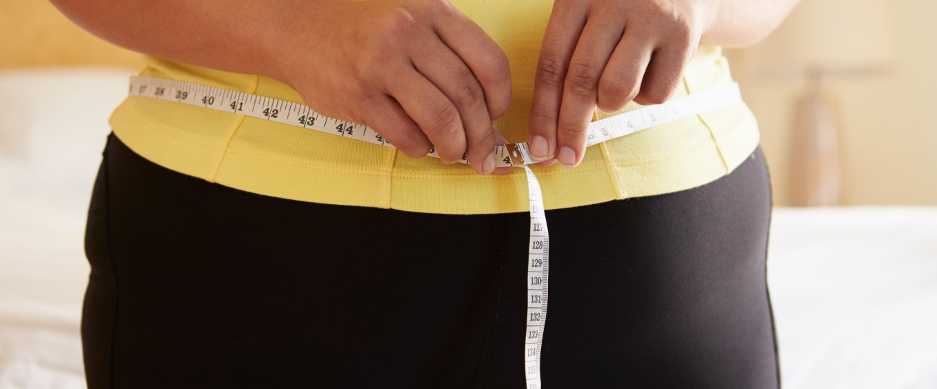 Woman in yellow top measuring waist