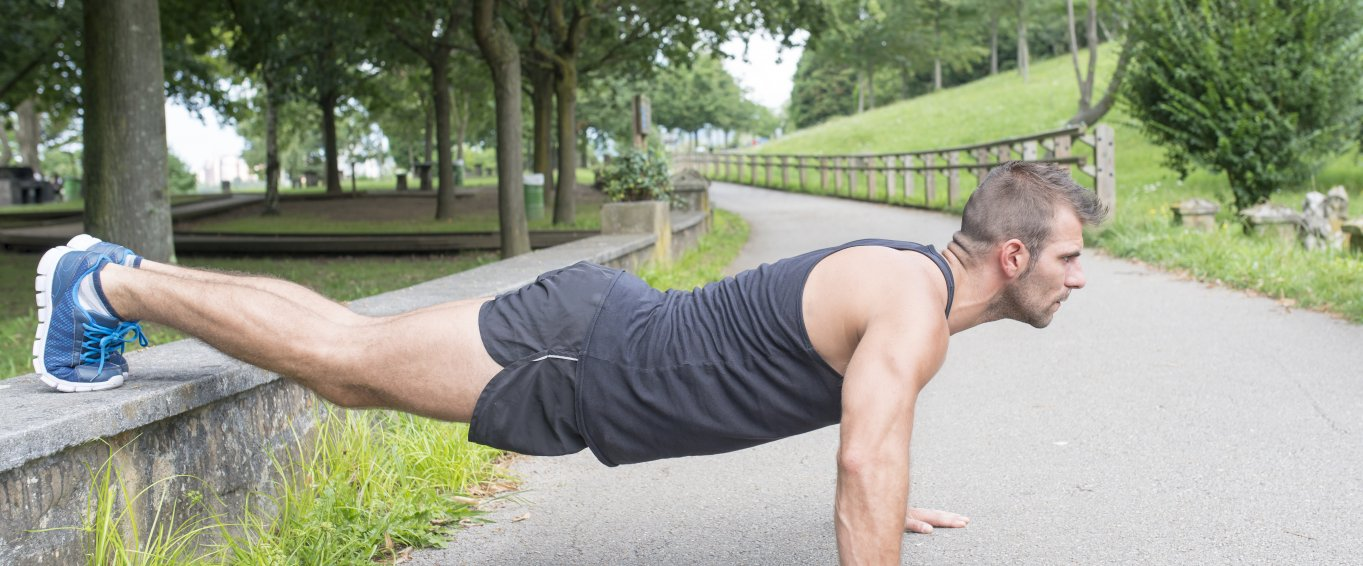 Man doing press up exercise on concrete path near green trees