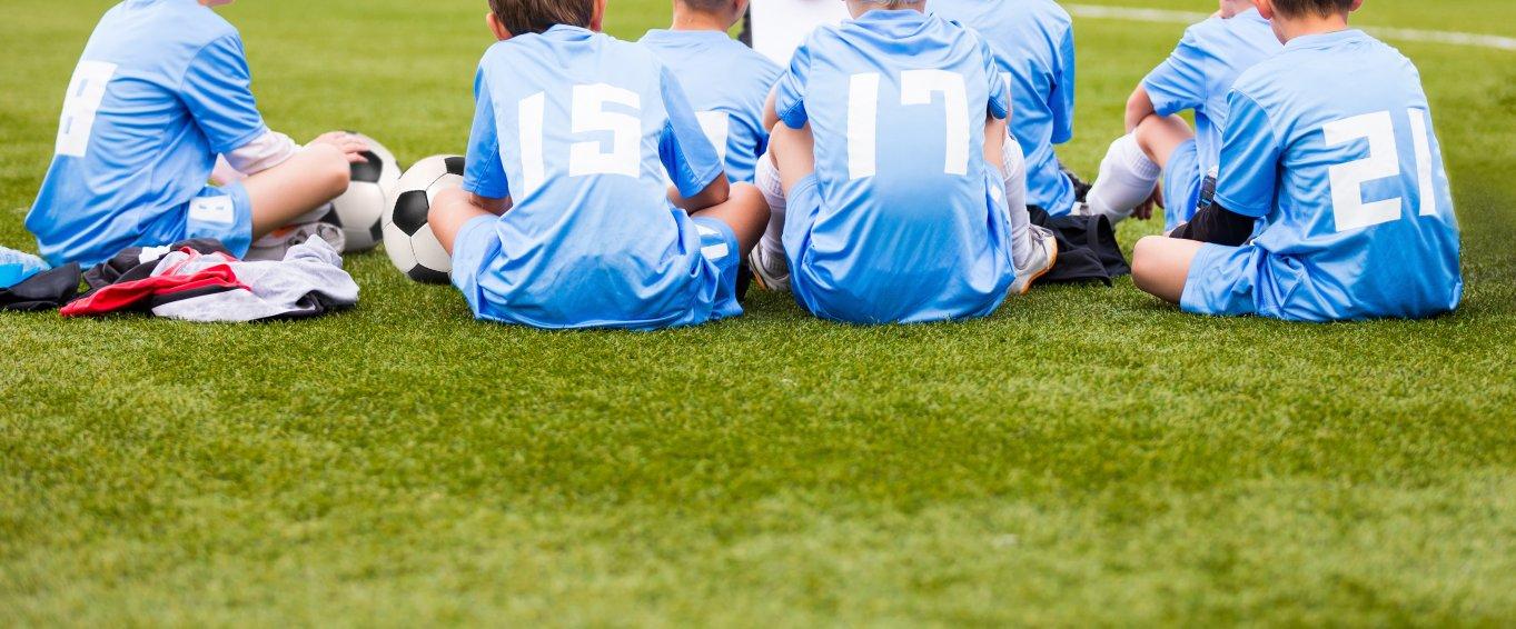 Boys football team sat listening to coach