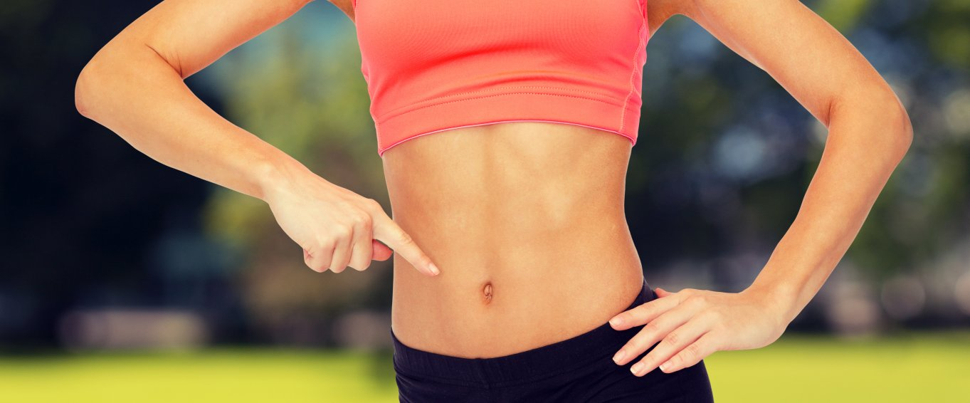 Athletic woman pointing to her stomach