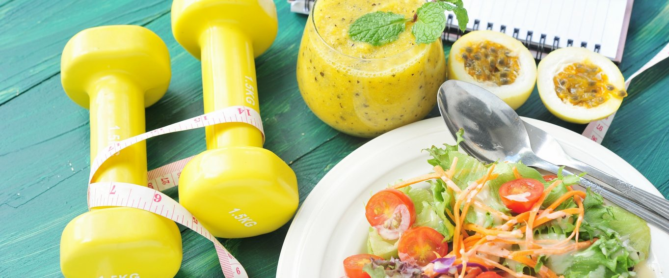 Healthy food and weights on a blue table