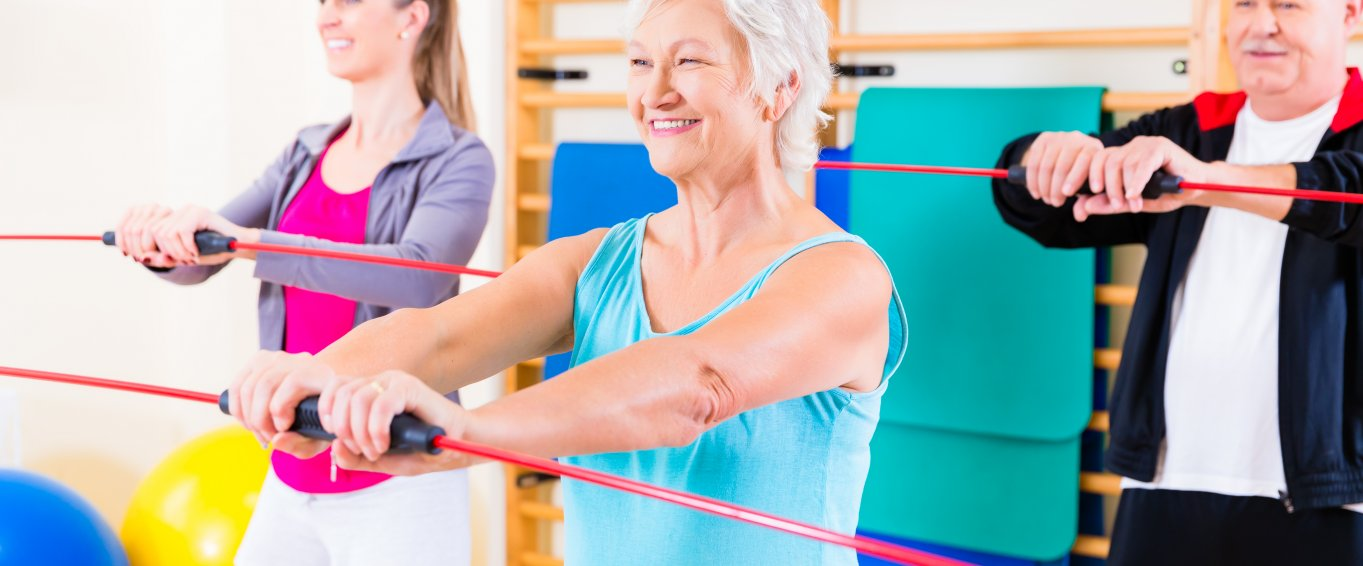 Group of older people and young girl exercising with barbell in gym