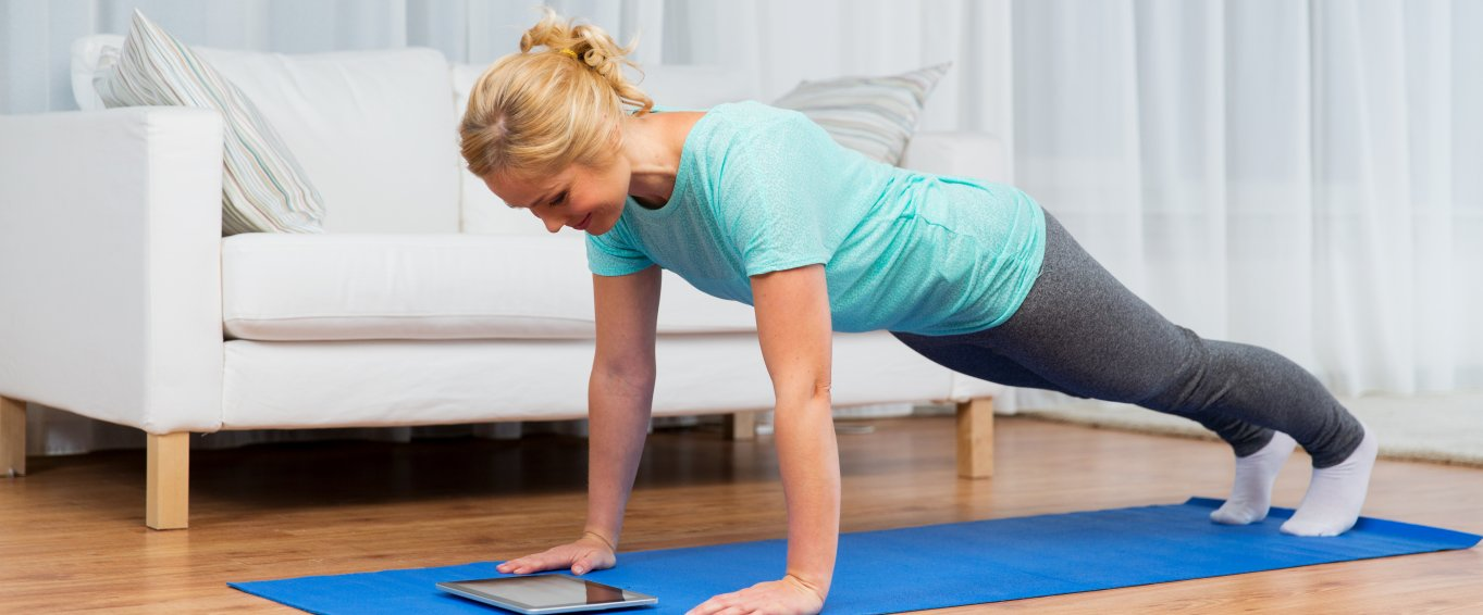 Woman doing press up while looking at tablet