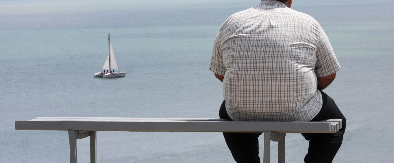 Obese man sitting on a bench, looking at a boat