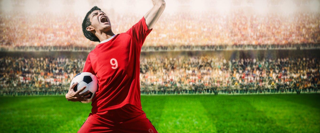 Male footballer celebrating goal infront of crowd