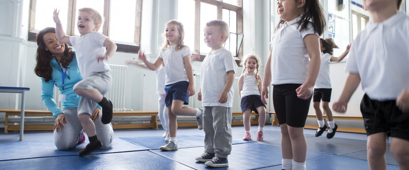 Primary School Pupils Exercising on Gym Mats