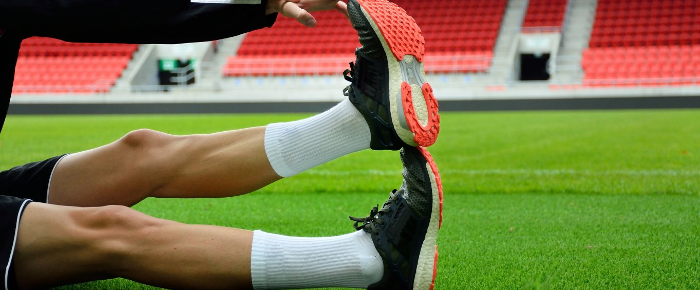 Footballer stretching out leg on football pitch