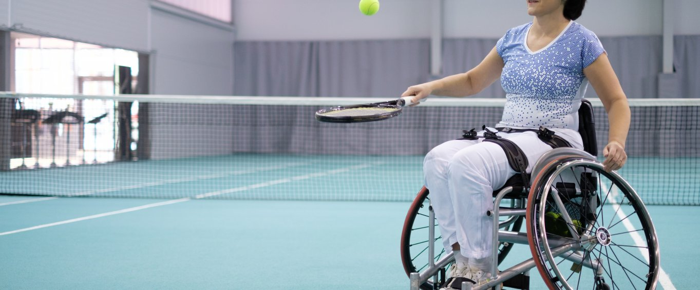 Woman in wheelchair playing tennis