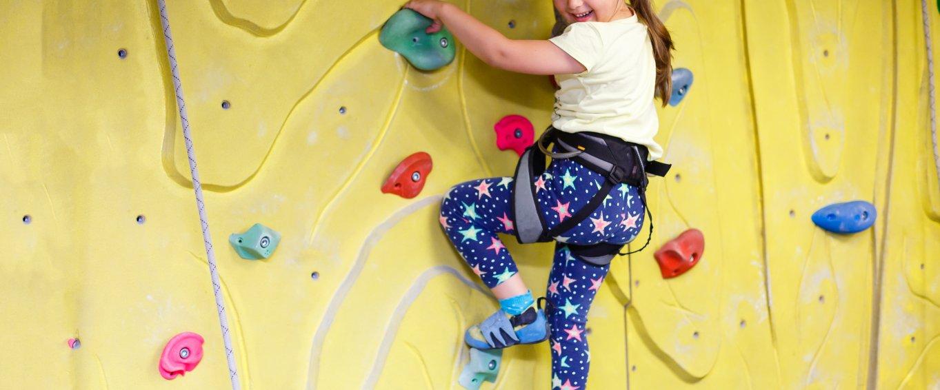 Young girl indoor rock climbing smiling