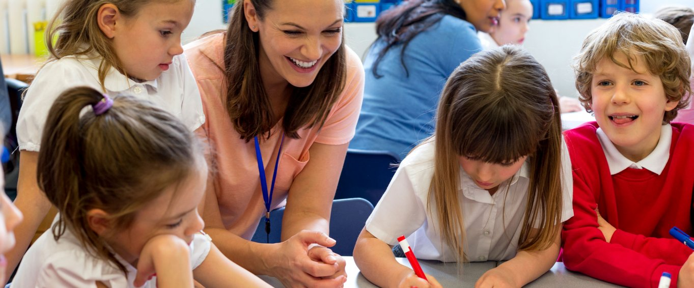Smiling Teacher Looking at Her Pupils' Drawings