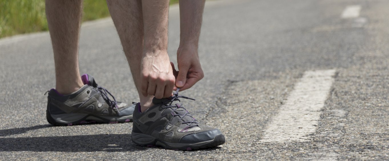 Man tying up running shoes