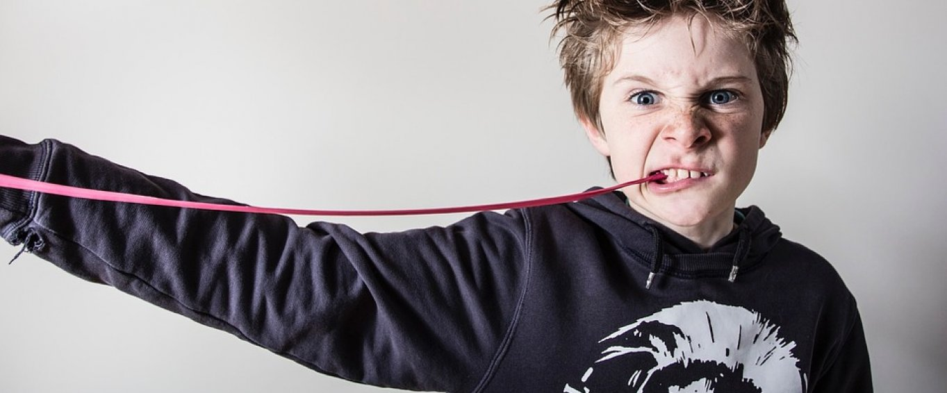 Young Boy Chewing Gum and Pulling a Fierce Face