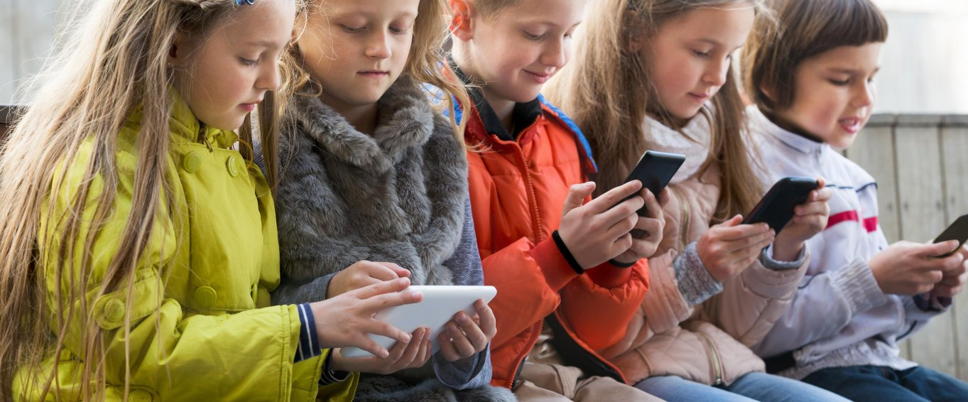 Young Children Staring At Their Mobile Phones