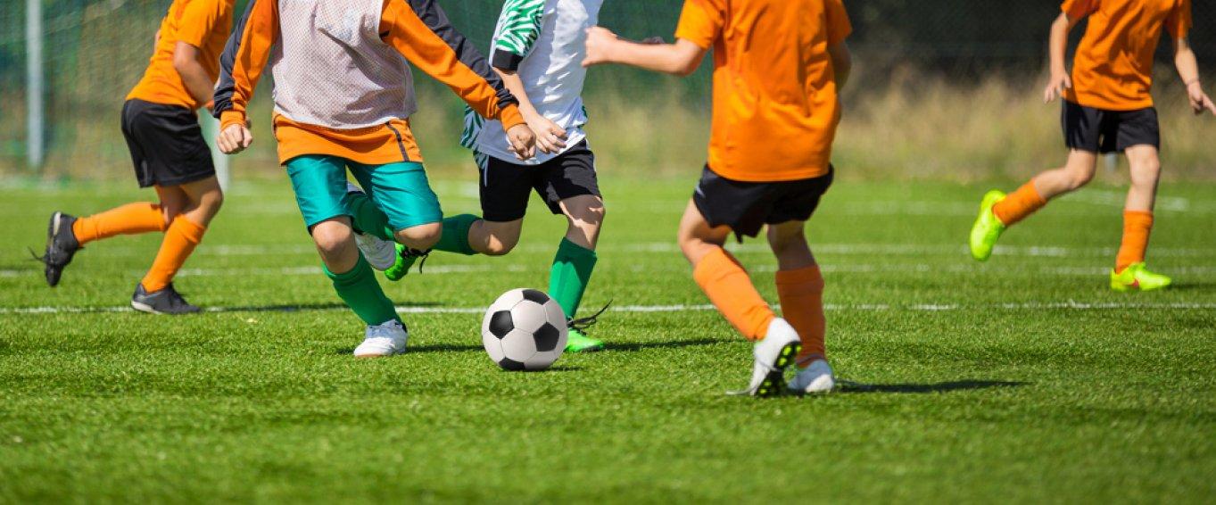 Kids Playing Football on a Pitch