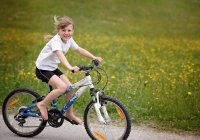 Young Girl Riding a Bicycle & Smiling
