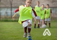 Young boy playing football Amaven