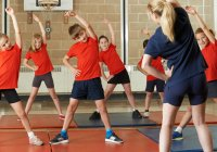 Young Children Stretching in Gym Class
