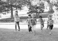 Children running up a grassy hill